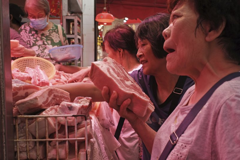 In this Thursday, May 16, 2019, file photo, customers buy frozen pork at a local market in Hong Kong. A case of African swine fever has been detected in a Hong Kong slaughterhouse, prompting the culling of all 6,000 pigs at the facility. Secretary for Food and Health Sophia Chan said in a statement Friday that the incurable virus was found in a single pig imported from a farm in Guangdong province in mainland China, where the monthslong outbreak has devastated herds. (AP Photo/Kin Cheung, File)