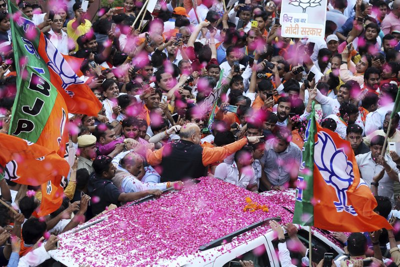 In this Thursday, May 23, 2019, file photo, India's ruling Bharatiya Janata Party (BJP) President Amit Shah is showered with flower petals as he arrives at the party office in new Delhi, India. Indian Prime Minister Narendra Modi's party claimed it had won reelection with a commanding lead in Thursday's vote count, while the stock market soared in anticipation of another five-year term for the pro-business Hindu nationalist leader. (AP Photo/Manish Swarup, File)
