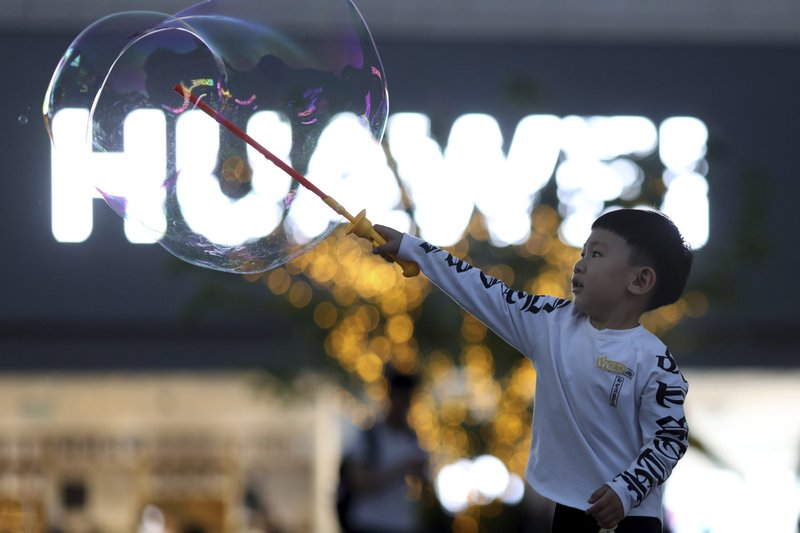 In this Monday, May 20, 2019, file photo, a child plays with bubbles near the logo for tech giant Huawei in Beijing. The Trump administration's sanctions against Huawei have begun to bite even though their dimensions remain unclear. U.S. companies that supply the Chinese tech powerhouse with computer chips saw their stock prices slump Monday, and Huawei faces decimated smartphone sales with the anticipated loss of Google's popular software and services. (AP Photo/Ng Han Guan, File)