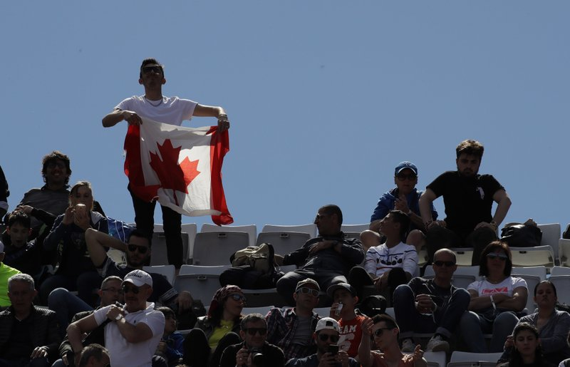 FILE - In this Thursday, May, 16, 2019 filer, A supporter shows a Canadian flag during the match between Serbia's Novak Djokovic and Canada's Denis Shapovalov at the Italian Open tennis tournament, in Rome. It's typically Canadian that Denis Shapovalov, Felix Auger-Aliassime and Bianca Andreescu are each children of immigrants. What's not typical is that they have all simultaneously broken into the world's elite ranks of tennis players _ and will all be worth watching when the French Open begins Sunday. (AP Photo/Alessandra Tarantino, File )