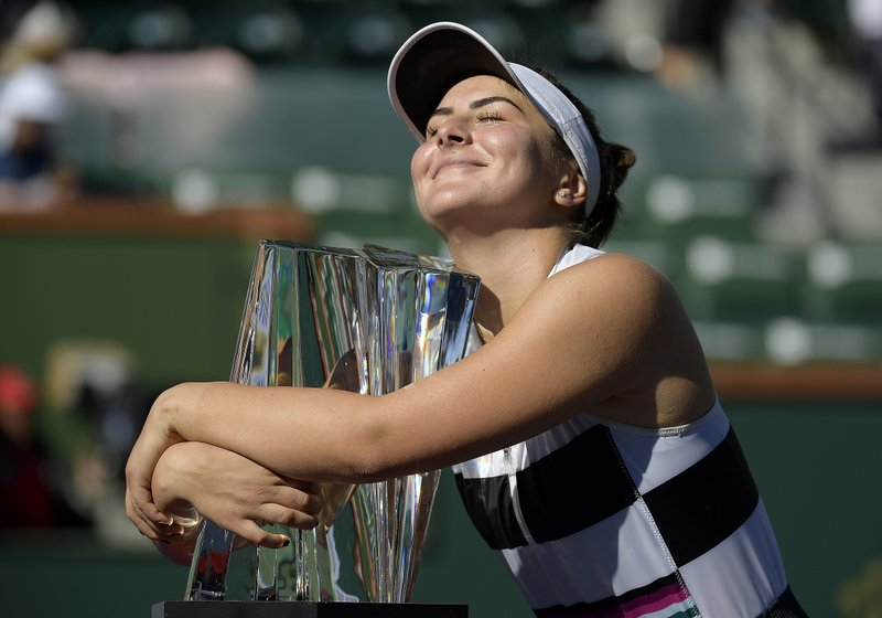 FILE - In this Sunday, March 17, 2019 file photo, Bianca Andreescu, of Canada, smiles as she hugs her trophy after defeating Angelique Kerber, of Germany, in the women's final at the BNP Paribas Open tennis tournament, in Indian Wells, Calif. It's typically Canadian that Denis Shapovalov, Felix Auger-Aliassime and Bianca Andreescu are each children of immigrants. What's not typical is that they have all simultaneously broken into the world's elite ranks of tennis players _ and will all be worth watching when the French Open begins Sunday. (AP Photo/Mark J. Terrill, File)