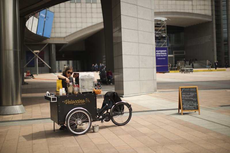 French coffee maker Noa waits for customer outside the European Parliament at the European quarter in Brussels, Thursday, May 23, 2019. Dutch and British voters were the first to have their say Thursday in elections for the European Parliament, starting four days of voting across the 28-nation bloc that pits supporters of deeper integration against populist euroskeptics who want more power for their national governments. (AP Photo/Francisco Seco)