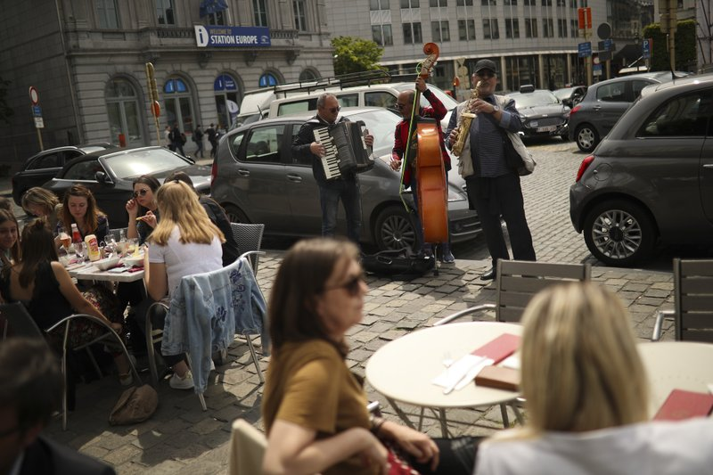 Romanian musicians perform for money in a restaurant area near the European Parliament at the European quarter in Brussels, Thursday, May 23, 2019. Dutch and British voters were the first to have their say Thursday in elections for the European Parliament, starting four days of voting across the 28-nation bloc that pits supporters of deeper integration against populist euroskeptics who want more power for their national governments. (AP Photo/Francisco Seco)