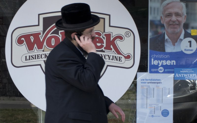 A man walks by an election poster in the window of a store in the Jewish quarter of Antwerp, Belgium, Thursday, May 23, 2019. Belgium, which has one of the oldest compulsory voting systems, will go to the polls for regional, federal and European elections on May 26, 2019. (AP Photo/Virginia Mayo)