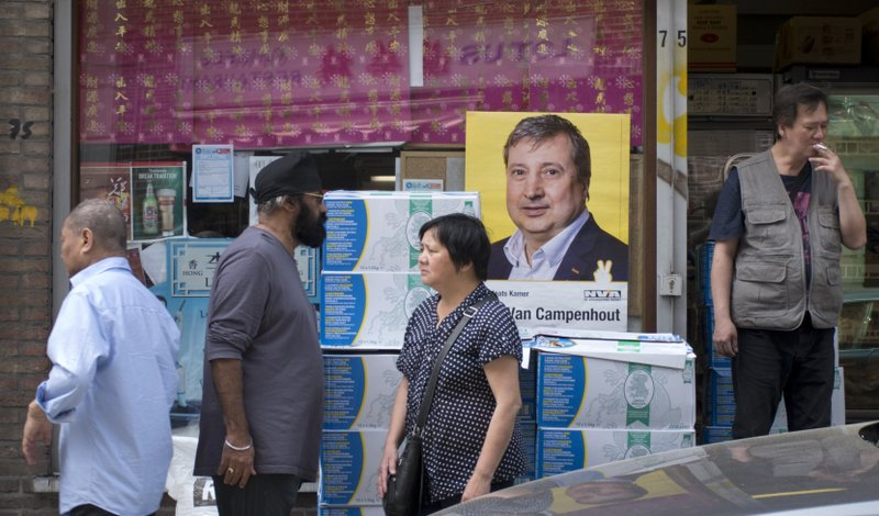 People walk by an election poster in the window of an Asian food store in the Chinatown quarter of Antwerp, Belgium, Thursday, May 23, 2019. Belgium, which has one of the oldest compulsory voting systems, will go to the polls for regional, federal and European elections on May 26, 2019. (AP Photo/Virginia Mayo)