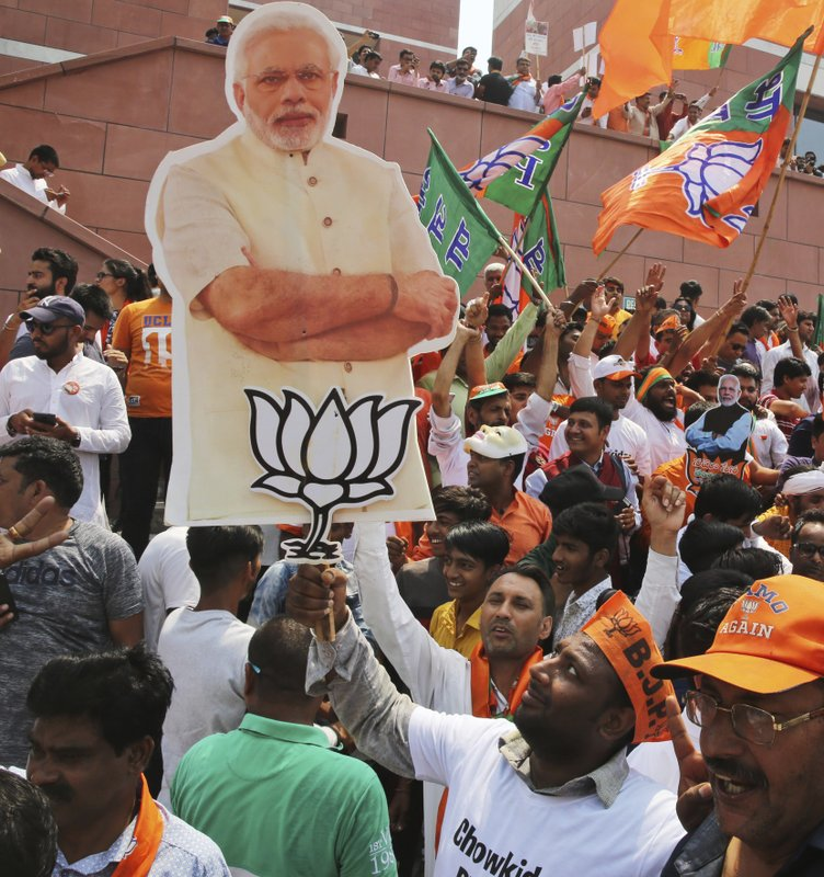 A Bharatiya Janata Party (BJP) supporter holds cutouts of Indian Prime Minister Narendra Modi and a symbol of his Bharatiya Janata Party and celebrate their party's victory in the general elections in New Delhi, India, Thursday, May 23, 2019. Indian Prime Minister Narendra Modi's party claimed it had won reelection with a commanding lead in Thursday's vote count, while the stock market soared in anticipation of another five-year term for the pro-business Hindu nationalist leader. (AP Photo/Manish Swarup)