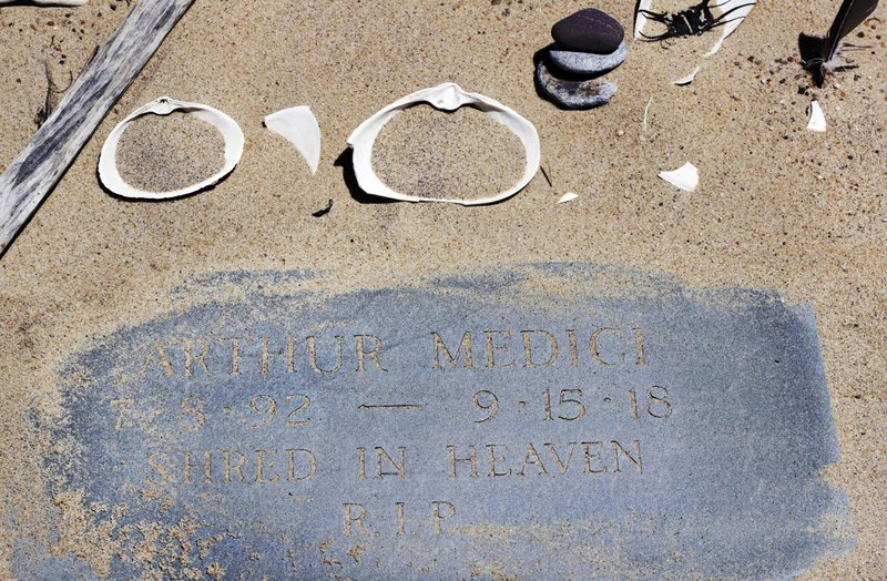 In the May 22, 2019, photo, a memorial stone for Arthur Medici, who died of injuries sustained in a shark attack while boogie boarding the previous summer, is adorned with a tiny cairn and seashells at Newcomb Hollow Beach in Wellfleet, Mass. Cape Cod beaches open this holiday weekend, just months after two shark attacks, one of which was fatal, rattled tourists, locals and officials. Some precautionary new measures, such as emergency call boxes, have yet to be installed along beaches where great whites are known to frequent. (AP Photo/Charles Krupa)