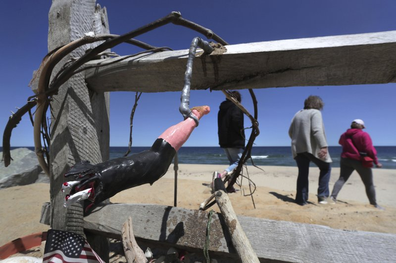 In this May 22, 2019, photo, three women pass a makeshift memorial at Newcomb Hollow Beach, where a boogie boarder was bitten by a shark and later died of his injuries the previous summer, in Wellfleet, Mass. Cape Cod beaches open this holiday weekend, just months after two shark attacks, one of which was fatal, rattled tourists, locals and officials. Some precautionary new measures, such as emergency call boxes, have yet to be installed along beaches where great whites are known to frequent. (AP Photo/Charles Krupa)