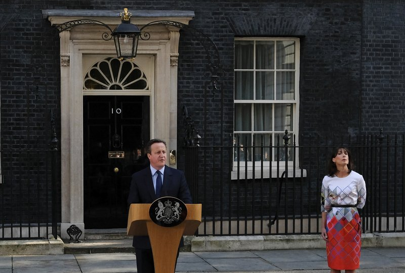 FILE - In this Friday, June 24, 2016 file photo, British Prime Minister David Cameron speaks outside 10 Downing Street, London as his wife Samantha looks on. Cameron announced his plan to step down, a day after Britain voted to leave the European Union in a referendum.  On Friday, May 24, 2019 announced she would resign as party leader, effective June 7, because of her inability to deliver on a referendum to leave the European Union. May has joined the ranks of Conservative prime ministers whose time in office has been overwhelmed — and cut short — by the issue of Europe. (AP Photo/Alastair Grant, File)