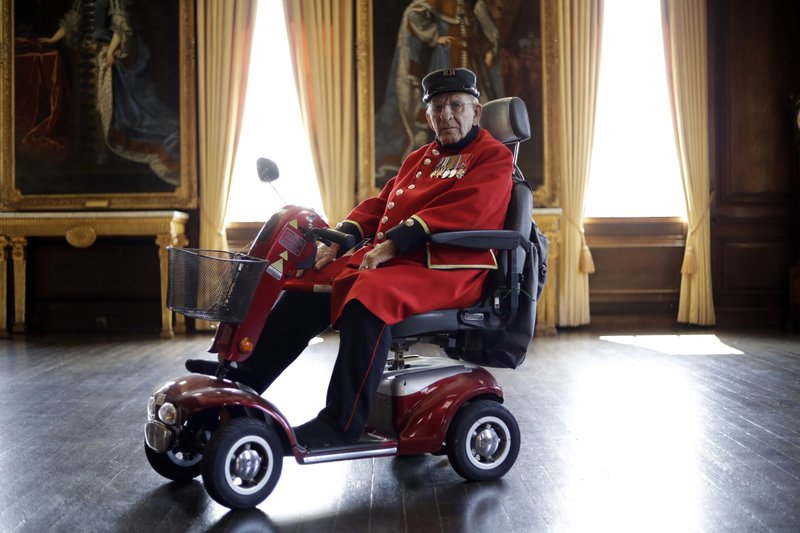 British Chelsea Pensioner and D-Day veteran Frank Mouque poses for a portrait during a D-Day 75th anniversary event in the State Apartments at the Royal Hospital Chelsea in London, May 13, 2019. Mouque, who can't hear well now and answered media questions by reading them from a piece of paper, was a Sapper and Corporal in the British Royal Engineers. On D-Day he landed on Sword beach and carried with him 21 pounds of explosives to blow down telegraph poles. (AP Photo/Matt Dunham)