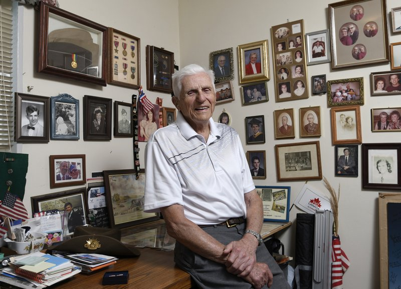 Steve Melnikoff who came ashore Normandy, France on D-Day with the 175th Regiment of the 29th Infantry Division, sits in his home in Cockeysville, Md., on May 21, 2019. His unit was part of the bloody campaign to capture the French town of Saint-Lo through fields marked by thick hedgerows that provided perfect cover for German troops. (AP Photo/Steve Ruark)