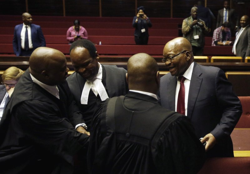 Former South African President Jacob Zuma, right, speaks with members of his legal team in the High Court in Pietermaritzburg, South Africa, Friday, May 24, 2019. Zuma is in court facing charges of corruption, money laundering and racketeering. (AP Photo/Themba Hadebe, Pool)