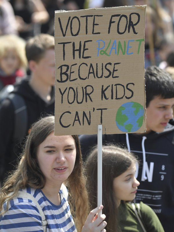 Young protestors hold a sign reading 'vote for the planet because your kids can't' ahead of the European elections during a climate strike of school students as part of the Fridays for Future movement in Frankfurt, Germany, Friday, May 24, 2019. (Boris Roessler/dpa via AP)