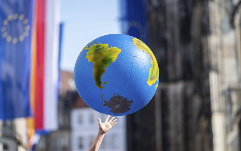 A protestor holds a symbolic earth in his hand during a climate strike of school students as part of the Fridays for Future movements Muenster, Germany, Friday, March 24, 2019. (Guido Kirchner/dpa via AP)