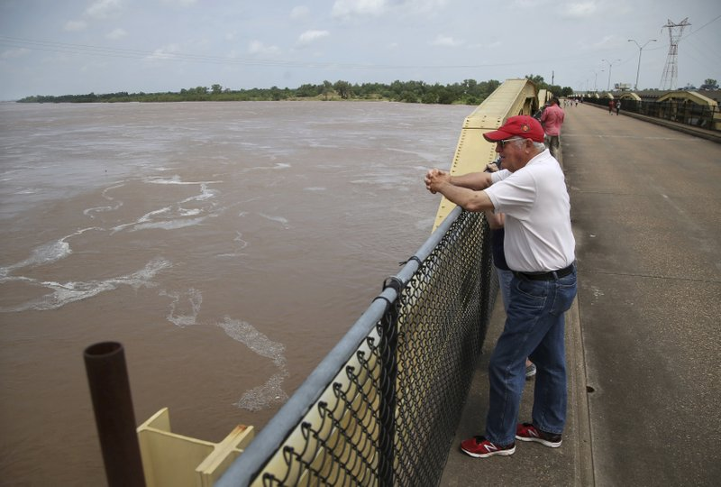 John MacDonald looks out over the swollen Arkansas River from the Memorial Drive pedestrian bridge in Bixby, Okla., on Thursday, May 23, 2019. Storms and torrential rains have ravaged the Midwest, from Texas through Oklahoma, Kansas, Nebraska, Iowa, Missouri and Illinois, in the past few days. (Matt Barnard/Tulsa World via AP)
