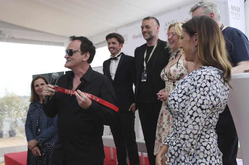 Director Quentin Tarantino poses for photographers with the Palm Dog collar award for the the dog Brandy that appeared in his film 'Once Upon a Time in Hollywood' at the 72nd international film festival, Cannes, southern France, Friday, May 24, 2019. (AP Photo/Petros Giannakouris)