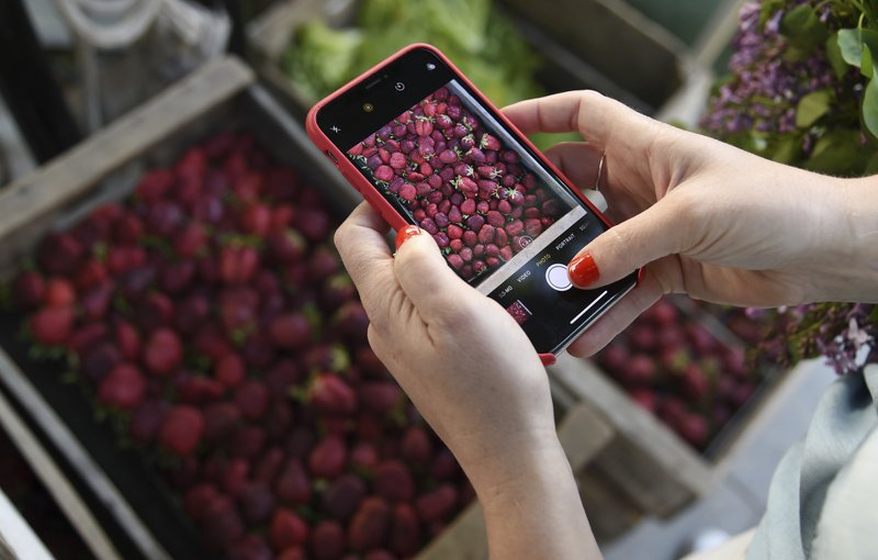 This April 10, 2019 photo shows Gaby Dalkin taking a photo of strawberries at Santa Monica Downtown Farmers Market in Santa Monica, Calif. Dalkin, the chef behind the popular Website and social media accounts, What's Gaby Cooking, is forging her own path. Every Monday she posts a live demo to Instagram as she cooks dinner which has become appointment viewing for some fans. Her husband films it and reads questions from viewers as she's cooking. (AP Photo/Chris Pizzello)