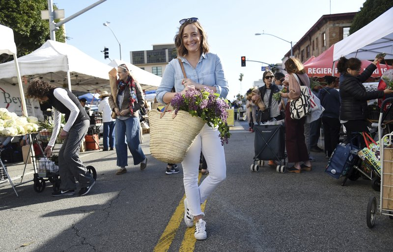 This April 10, 2019 photo shows Gaby Dalkin at Santa Monica Downtown Farmers Market in Santa Monica, Calif. Dalkin, the chef behind the popular Website and social media accounts, What's Gaby Cooking, is forging her own path. Every Monday she posts a live demo to Instagram as she cooks dinner which has become appointment viewing for some fans. Her husband films it and reads questions from viewers as she's cooking. (AP Photo/Chris Pizzello)