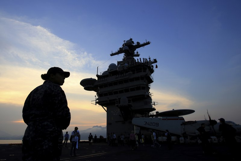 FILE - In this Monday, March 5, 2018 file photo, people stand on the deck of the USS Carl Vinson aircraft carrier as it docks in Danang bay, Vietnam. A U.S. sailor has pleaded guilty to espionage and sentenced to three years after admitting he took classified information about a Navy's nuclear-powered warship and planned to give it to a journalist and then defect to Russia officials said Friday, May 24, 2019. Jeff Houston of the Naval Criminal Investigative Service or NCIS said that U.S. Navy Petty Officer 2nd Class Stephen Kellogg III wished to publish an expose on waste within the military and admitted he wanted to share the information with Russians. Kellogg, who joined the Navy in 2014 served aboard the USS Carl Vinson from 2016 to 2018. (AP Photo/Hau Dinh, File)