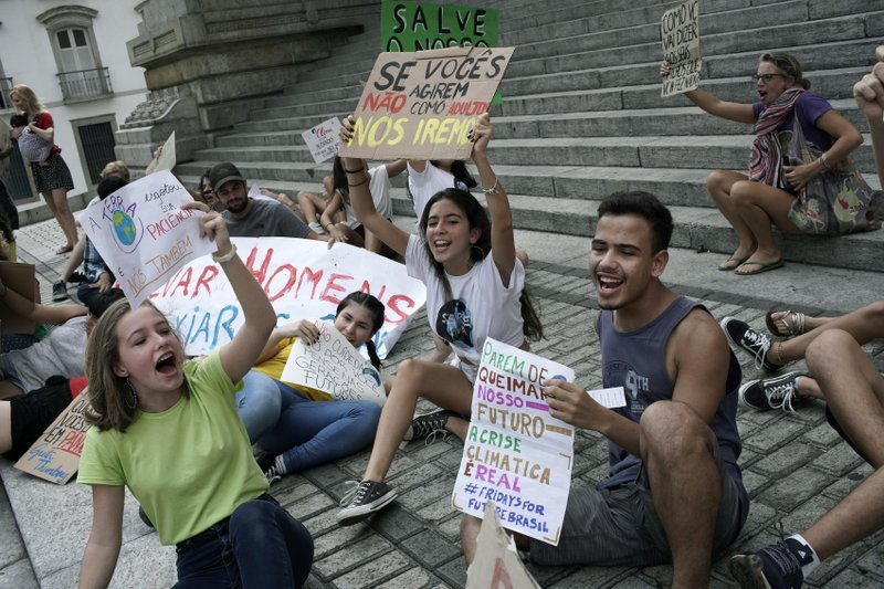 Students protest President Jair Bolsonaro's environmental policies in front the state legislature in Rio de Janeiro, Brazil, Friday, May 24, 2019. A small group of students gathered outside the state legislature to deliver a letter dated from the future in which they lamented Brazil's loss of coastline, rainforests and species. (AP Photo/Silvia Izquierdo)