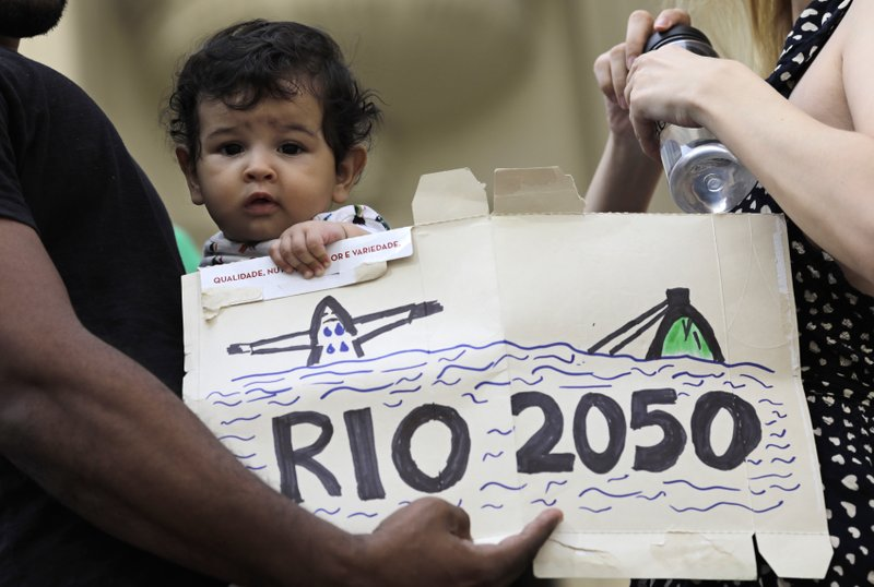 A baby holds a sign that reads