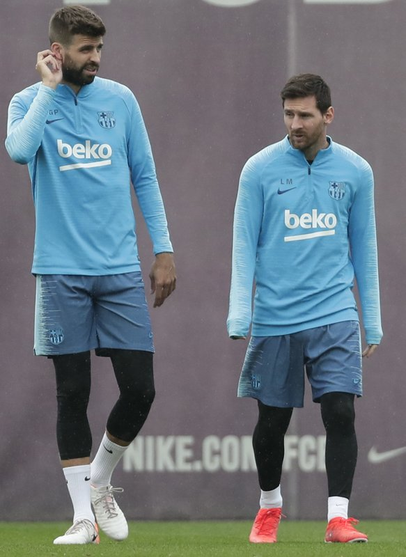 FC Barcelona's Lionel Messi, right, and Gerard Pique take part in a training session at the Sports Center FC Barcelona Joan Gamper in Sant Joan Despi, Spain, Friday, May 24, 2019. FC Barcelona will play against Valencia in the Spanish Copa del Rey soccer match final on Saturday. (AP Photo/Manu Fernandez)
