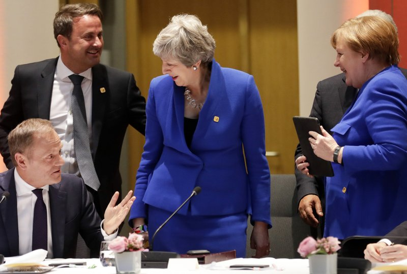 In this Wednesday, April 10, 2019 file photo, European Council President Donald Tusk, left, speaks with British Prime Minister Theresa May, center, German Chancellor Angela Merkel, right, and Luxembourg's Prime Minister Xavier Bettel, second left, prior to a dinner during an EU summit in Brussels. (Olivier Hoslet, Pool Photo via AP, File)