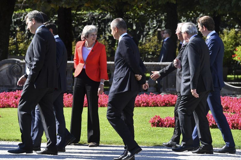 In this Thursday, Sept. 21, 2018 file photo, British Prime Minister Theresa May speaks to other heads of government after a group photo at an EU summit in Salzburg, Austria. (AP Photo/Kerstin Joensson, File)