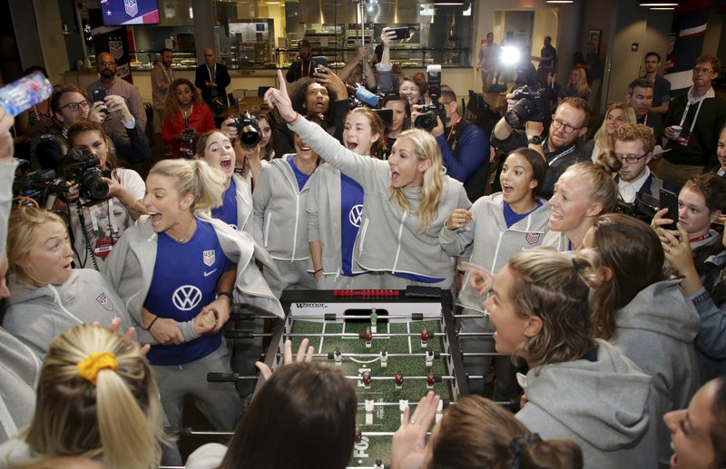 Member of the United States women's national soccer team react while while playing a foosball table featuring their likenesses during the team's Women's World Cup media day in New York, Friday, May 24, 2019. (AP Photo/Seth Wenig)