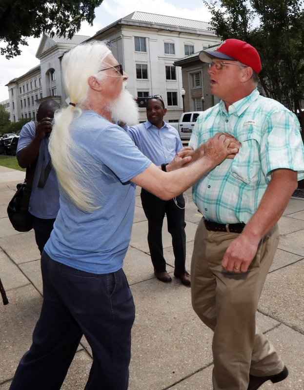 An abortion rights advocate who did not want to be identified detains Coleman Boyd, right, an anti-abortion supporter, as he tries to disrupt a gathering of rights advocates who gathered at the Capitol in Jackson, Miss., to voice their opposition to the state legislature passing a new law that prohibits most abortions once a fetal heartbeat can be detected, Tuesday, May 21, 2019. (AP Photo/Rogelio V. Solis)