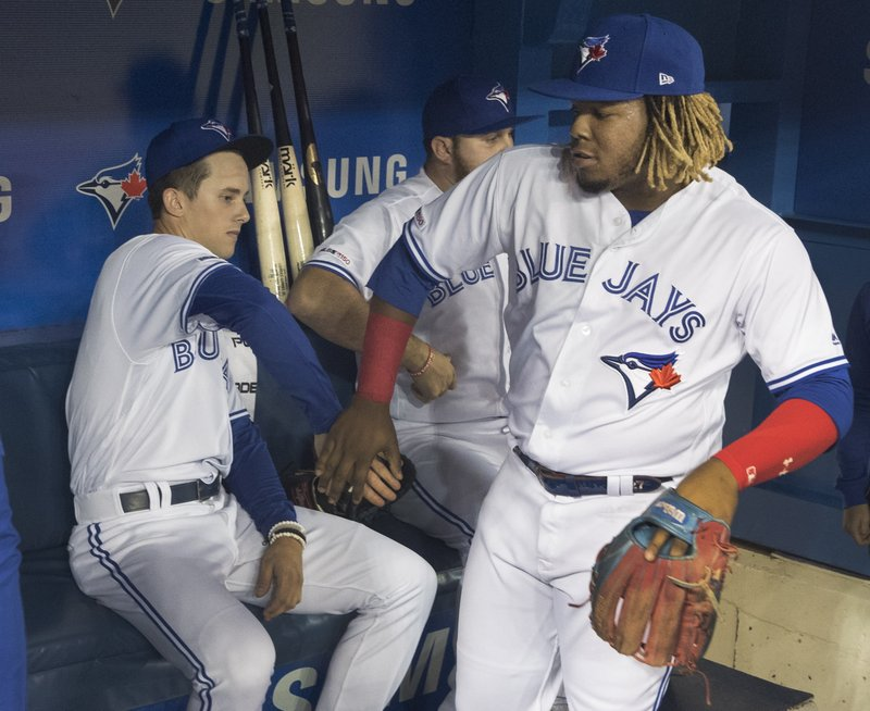 Toronto Blue Jays' Cavan Biggio, left, and Vladimir Guerrero Jr. joke around before the team's baseball game against the San Diego Padres on Friday, May 24, 2019, in Toronto. (Fred Thornhill/The Canadian Press via AP)