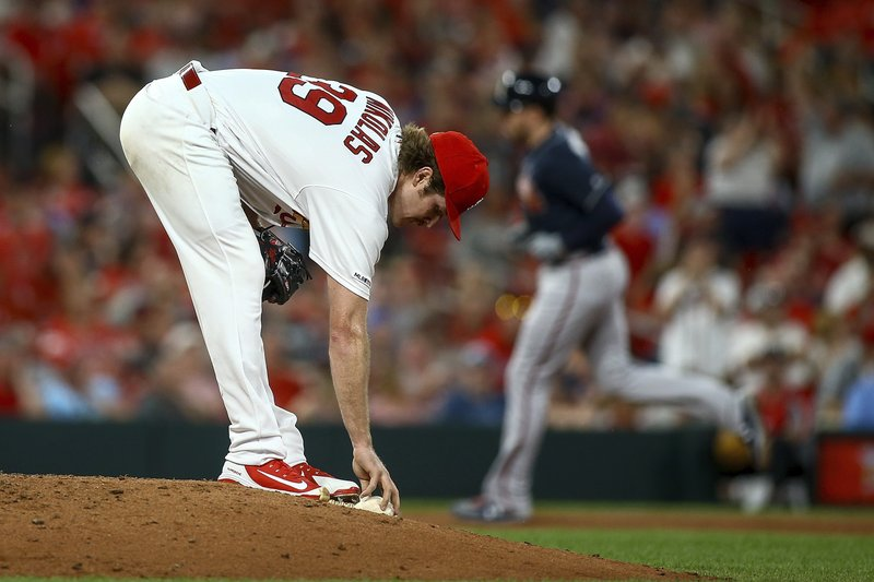 St. Louis Cardinals starting pitcher Miles Mikolas (39) reaches for the rosin bag as Atlanta Braves' Freddie Freeman, background right, runs the bases after hitting a solo home run during the sixth inning of a baseball game Friday, May 24, 2019, in St. Louis. (AP Photo/Scott Kane)