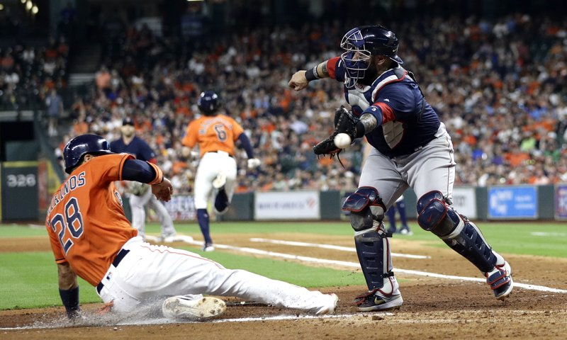 Houston Astros' Robinson Chirinos (28) scores as Boston Red Sox catcher Sandy Leon reaches for the throw from shortstop Xander Bogaerts during the fourth inning of a baseball game Friday, May 24, 2019, in Houston. Bogaerts was charged with a throwing error on the play.(AP Photo/David J. Phillip)