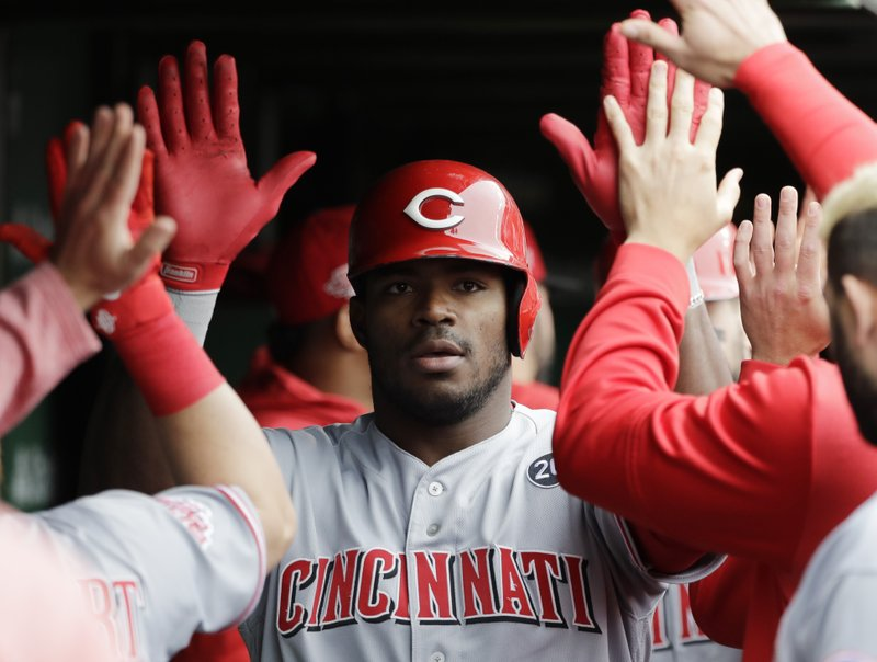 Cincinnati Reds' Yasiel Puig celebrates with teammates after hitting a two-run home run against the Chicago Cubs during the sixth inning of a baseball game Friday, May 24, 2019, in Chicago. (AP Photo/Nam Y. Huh)