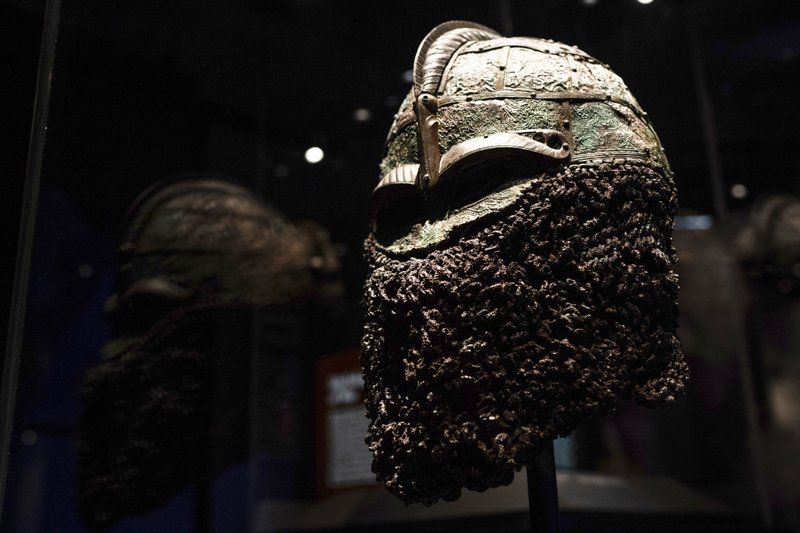 A Viking battle helmet with a face guard sits on display inside of the American Swedish Institute's