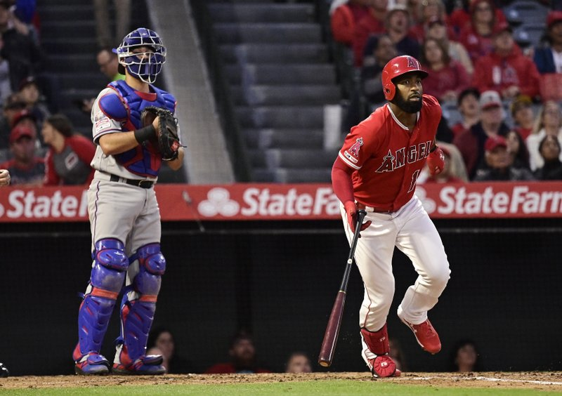 Los Angeles Angels' Brian Goodwin, right, starts to run to first after hitting a two-run home run while Texas Rangers catcher Isiah Kiner-Falefa looks on during the third inning of a baseball game Friday, May 24, 2019, in Anaheim, Calif. (AP Photo/Mark J. Terrill)
