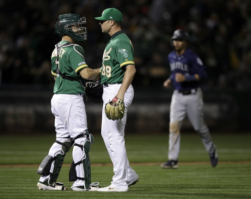 Oakland Athletics' Blake Treinen, right, and Nick Hundley celebrate the team's 6-2 win over the Seattle Mariners in a baseball game Friday, May 24, 2019, in Oakland, Calif. (AP Photo/Ben Margot)