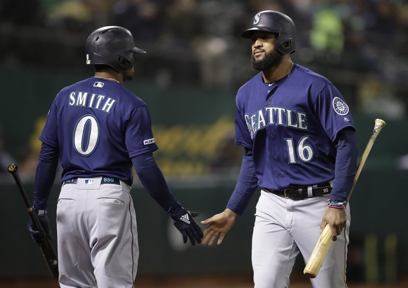 Seattle Mariners' Domingo Santana, right, is congratulated by Mallex Smith (0) after scoring against the Oakland Athletics during the seventh inning of a baseball game Friday, May 24, 2019, in Oakland, Calif. (AP Photo/Ben Margot)