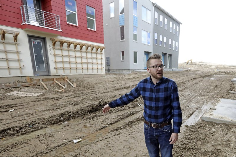 In this April 13, 2019, photo, Parry Harrison, 26, speaks during an interview outside his townhouse in the Daybreak development, in South Jordan, Utah. Harrison bought a townhouse in Daybreak for $309,000 in March, using proceeds from the sale of a house that appreciated a robust 25% in the two years he owned it. (AP Photo/Rick Bowmer)