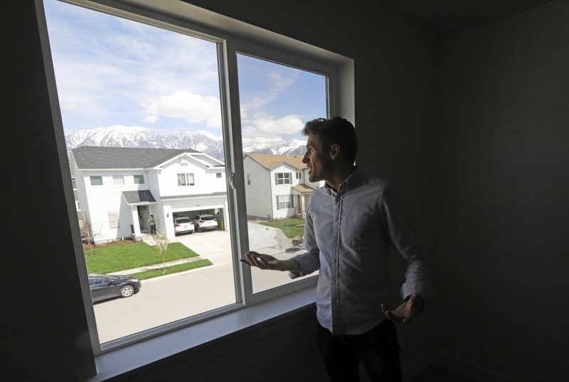 In this April 27, 2019, photo, Andy Proctor peers through the window at his new home in Vineyard, Utah. For some millennials looking to buy their first home, the hunt feels like a race against the clock. Andy and his wife, Stacie made a successful offer on a three-bedroom house for $438,000. (AP Photo/Rick Bowmer)