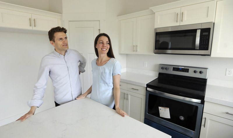 In this April 27, 2019, photo, Andy and Stacie Proctor stand in their new home in Vineyard, Utah. For some millennials looking to buy their first home, the hunt feels like a race against the clock. The Proctors ultimately made a successful offer on a three-bedroom house for $438,000. (AP Photo/Rick Bowmer)