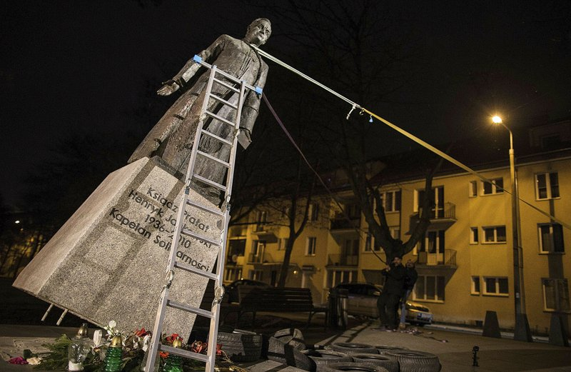 FILE  - In this Thursday Feb. 21, 2019 file photo, activists in Poland pull down a statue of a prominent deceased priest, Father Henryk Jankowski, who allegedly abused minors sexually, in Gdansk, Poland. A documentary film with testimony by victims of clerical abuse in Poland is so harrowing that it has forced an unprecedented reckoning with the problem in one of Europe's most deeply Catholic societies. (Bartek Sabela/Gazeta Wyborcza, via AP, File)
