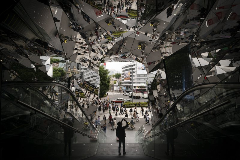 A man takes pictures in the entrance way to a shopping mall decorated with mirrors Saturday, May 18, 2019, in Harajuku district of Tokyo. (AP Photo/Jae C. Hong)