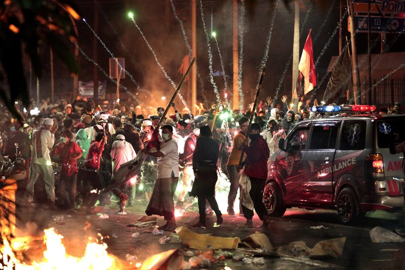 Firecrackers explode near supporters of presidential candidate Prabowo Subianto during clashes with the police in Jakarta, Indonesia, Wednesday, May 22, 2019. Seven people have died in election violence in the Indonesian capital, police said Thursday, as calm returned to the city and the losing presidential candidate prepared the challenge the result in court. (AP Photo/Dita Alangkara)