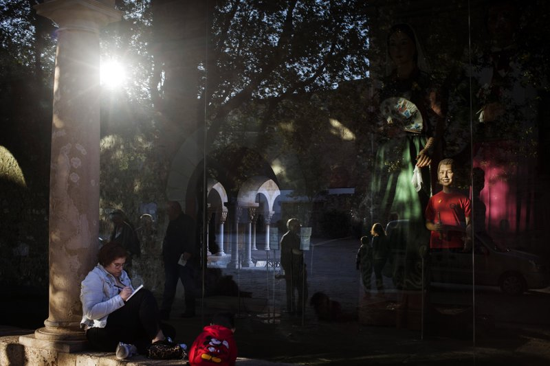 A woman writes as people are reflected in a window of The Monastery of Sant Cugat, a Benedictine abbey in Sant Cugat del Valles, Catalonia, Spain, on Monday, May 20, 2019. (AP Photo/Emilio Morenatti)