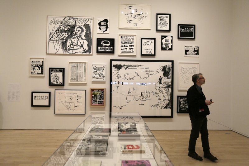 In this photo taken May 15, 2019, a man looks at a display of work from the 1980's at the exhibition