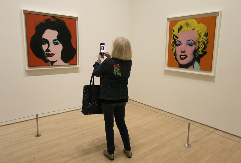 In this photo taken May 15, 2019, a woman records the female icon pieces of Elizabeth Taylor and Marilyn Monroe at the exhibition