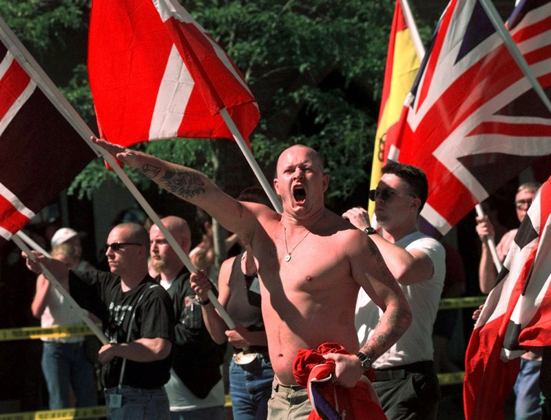 FILE - In this July 18, 1998, file photo, Karl Wolf raises his arm in a Nazi salute as he marches through the streets of Coeur d'Alene, Idaho, where scores of police in riot gear stood between parading white supremacists and protesters who jeered at the Aryan Nations marchers. Nearly two decades after the Aryan Nations compound was demolished in Idaho, far-right extremists are maintaining a presence in the Pacific Northwest. White nationalism has been on the rise across the U.S., but it has particular resonance along the Idaho-Washington border. (AP Photo/Elaine Thompson, File)