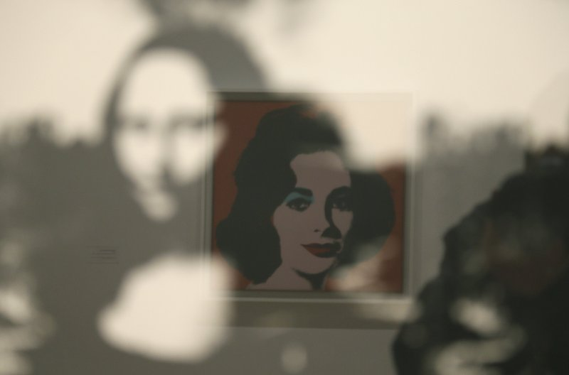 In this photo taken Wednesday, May 15, 2019, in a display of female icons, Elizabeth Taylor is reflected in an image of the Mona Lisa at the exhibition,