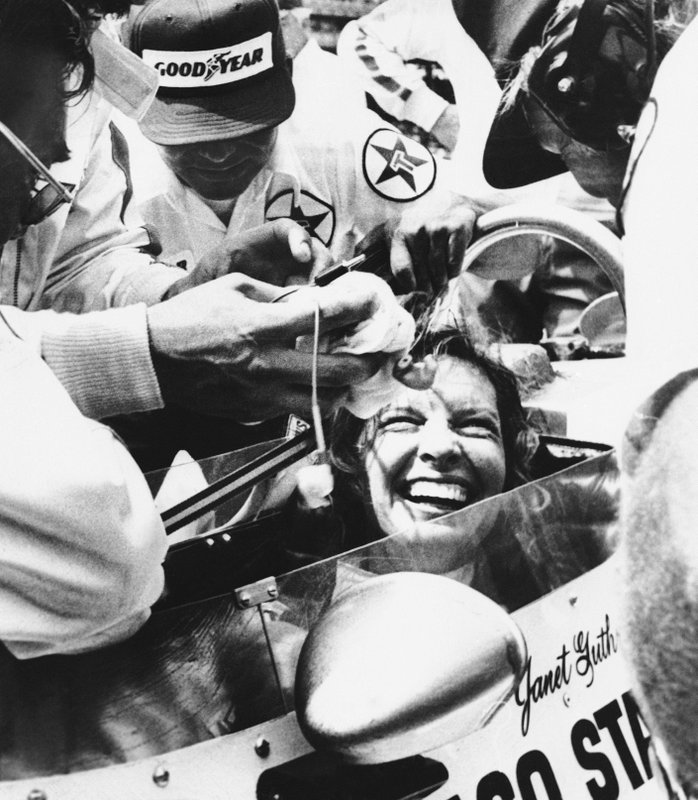 FILE - In this May 28, 1978, file photo, Janet Guthrie is all smiles as her pit crew swarms around her following the 62nd running of the Indianapolis 500 auto race in Indianapolis, Ind. She wanted a spot in the biggest race in the world and her competitors didn't want her anywhere near the Indianapolis 500. It took Guthrie two tries to earn a starting spot, she became the first woman to race in the Indy 500 in 1977, and even longer to change minds about her talent. (AP Photo/File)